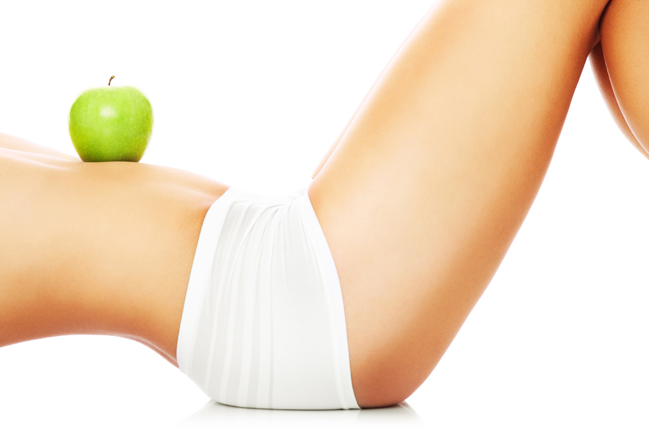 A picture of a woman holding a green apple on her fit belly